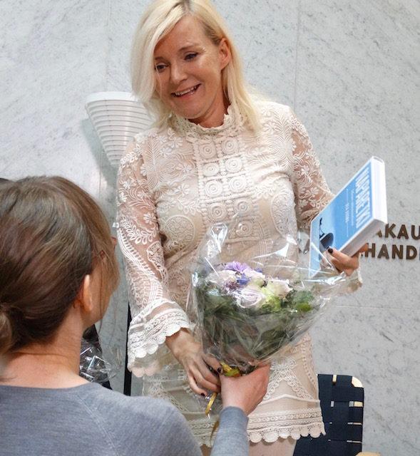 Liisa Pihlaja ojentaa onnittelukukat Bea Uusmalle.