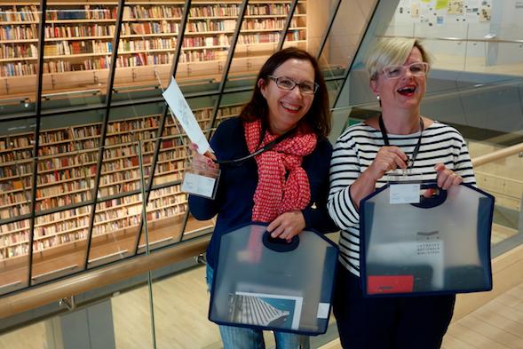 Kirsi ja Airi ihastelivat hienoja kirjaston kirjaseiniä.